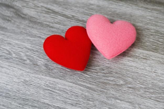 Colore rosso e rosa del cuore su fondo di legno