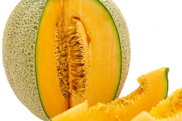 Colori brillanti del melone del primo piano che sono girati e pezzi isolati su fondo bianco.