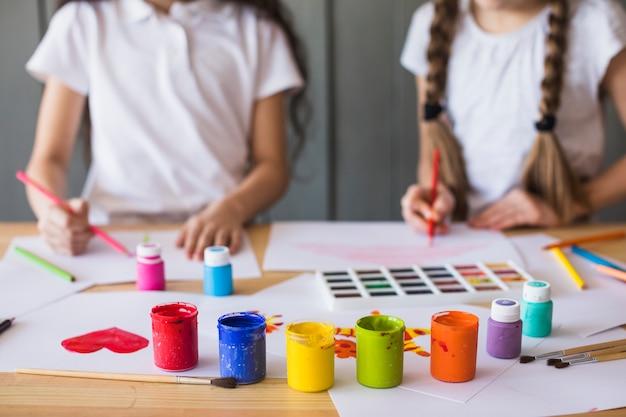 Colori di vernice colorata davanti a una ragazza che dipinge sul libro bianco sul tavolo