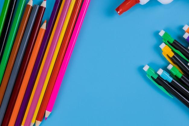 Colori la matita isolata su fondo blu, concetto di arte di istruzione.