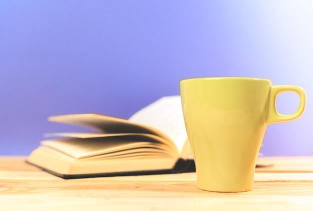 Colori la tazza di tè con i libri sulla tavola