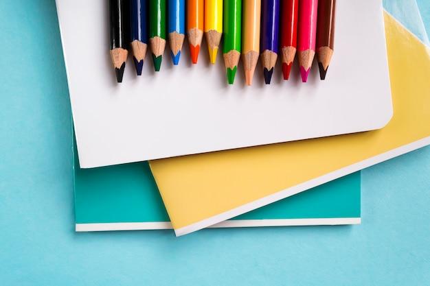 Colori le matite ed i taccuini della scuola sull'azzurro con lo spazio della copia. materiale scolastico.