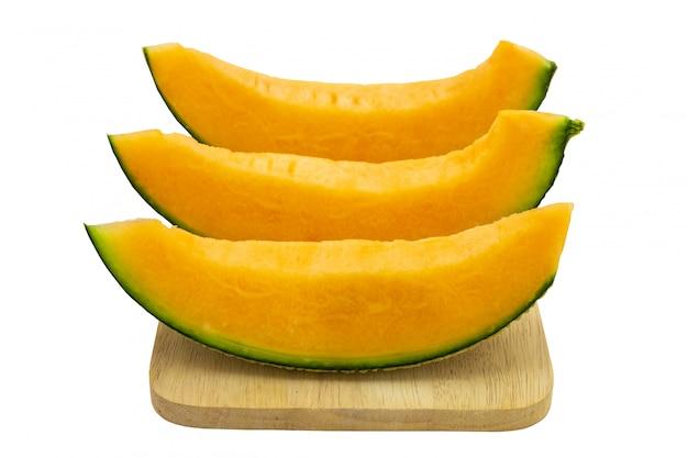 Colori luminosi del melone del primo piano che è pezzi sul vassoio di legno isolato su fondo bianco.