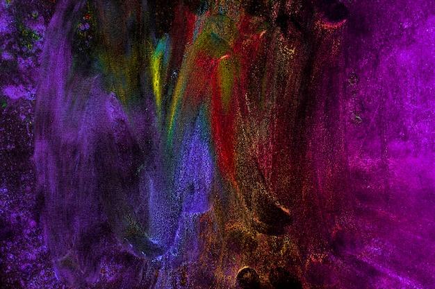 Colori multicolori di holi macchiati con la mano su fondo nero