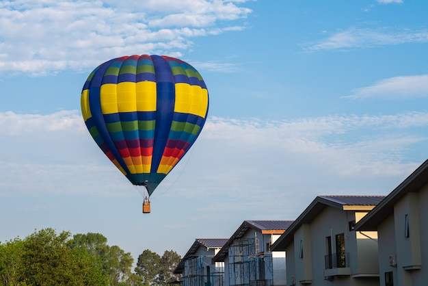 Colourful del pallone su cielo blu con il villaggio di casa