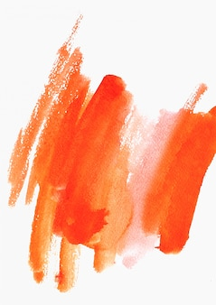 Colpi di colore arancione dell'acquerello di vernice su bianco