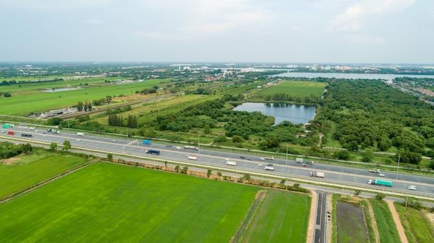 Colpo aereo delle automobili che guidano sui campi di un'autostrada verde