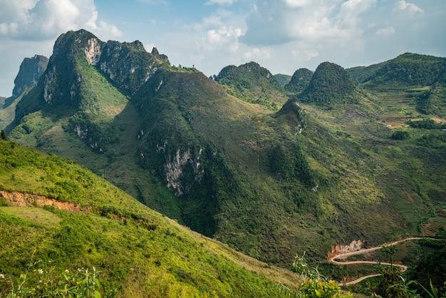 Colpo aereo di alte montagne verdi sotto il cielo nuvoloso nel vietnam