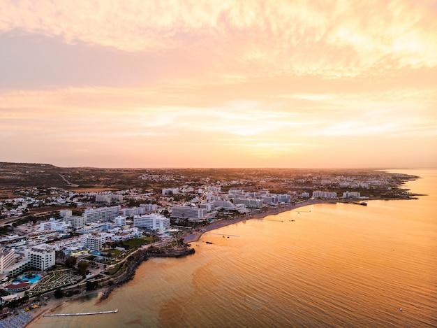 Colpo aereo drone del tramonto sopra la città di protaras