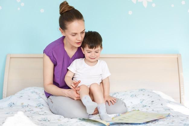 Colpo al coperto di affettuosa giovane madre tiene e abbraccia il suo piccolo figlio, guarda attentamente il libro con immagini colorate