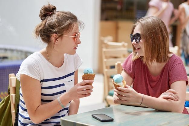 Colpo al coperto di giovani amiche felici si guardano gioiosamente, mangiano il gelato, discutono qualcosa di piacevole con le espressioni allegre, si siedono contro l'accogliente interno del caffè. concetto di compagnia