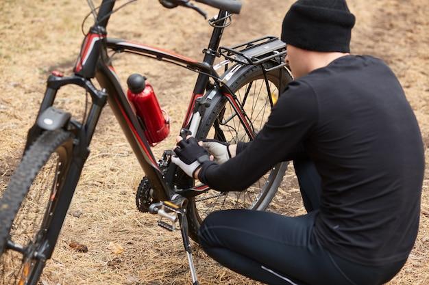 Colpo all'aperto dell'uomo che ripara il suo icycle nel campo o nella foresta, avendo la puntura della bicicletta sul modo, tipo che posa indietro