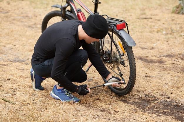 Colpo all'aperto dell'uomo che ripara la sua bicicletta nel campo o nella foresta, sedendosi sulla terra, pompando la gomma con attrezzatura speciale