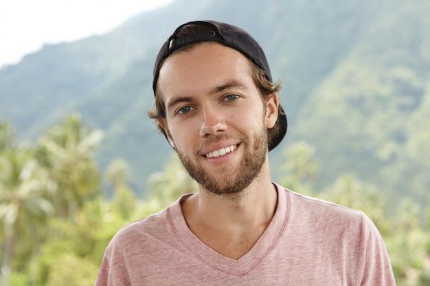 Colpo all'aperto di giovane uomo caucasico con la barba che si distende all'aria aperta, circondato da una splendida cornice di montagna e foresta pluviale