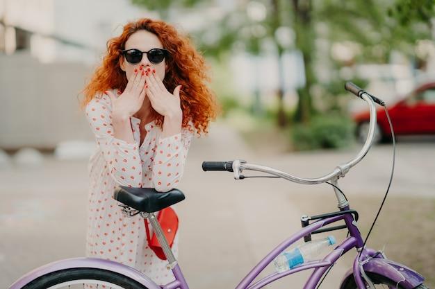 Colpo all'aperto di splendida femmina dai capelli rossi copre la bocca con entrambe le palme