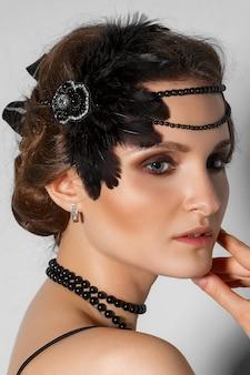 Colpo alla testa del modello con pennacchio in capelli e perla nera nel profilo
