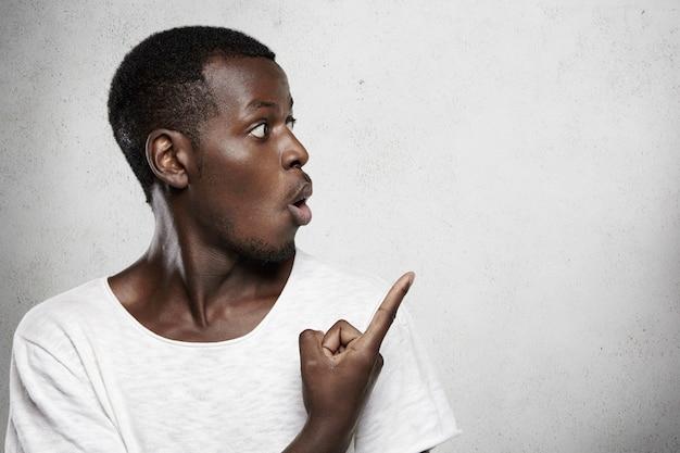 Colpo alla testa di un giovane cliente dalla pelle scura di bell'aspetto che guarda lontano il muro bianco, puntando il dito contro lo spazio della copia per il tuo contenuto promozionale, dicendo wow o omg, sorpreso dalle informazioni