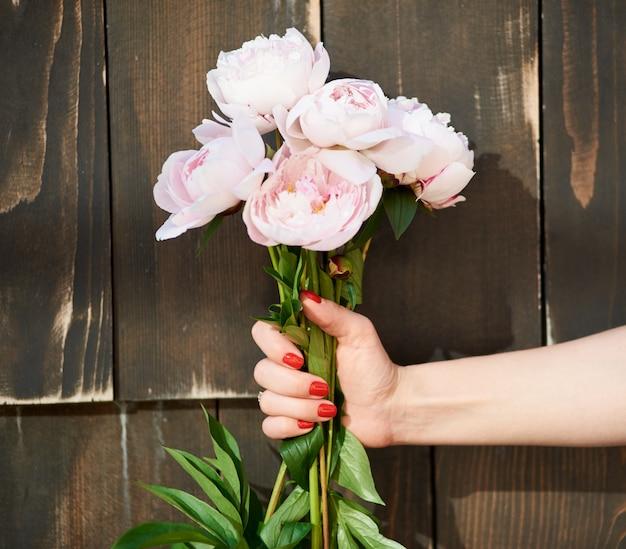 Colpo alto vicino potato di un mazzo delle peonie rosa in un fondo di legno della mano femminile