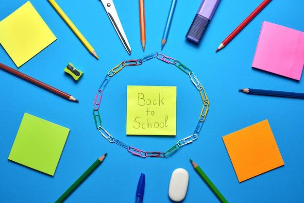 Colpo ambientale dei rifornimenti di scuola sull'azzurro vibrante