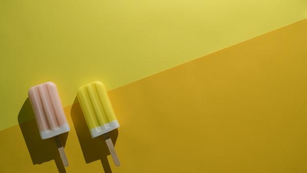 Colpo ambientale del concetto minimo di estate con i ghiaccioli di sapore della fragola e del limone