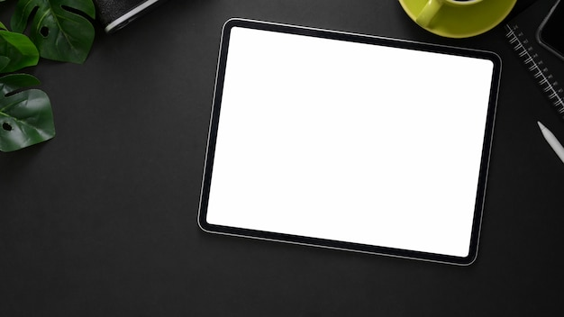 Colpo ambientale del posto di lavoro con la compressa digitale, gli articoli per ufficio e la tazza di caffè sulla tavola nera