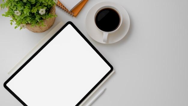 Colpo ambientale del posto di lavoro con la compressa digitale, la tazza di caffè, le decorazioni e lo spazio della copia