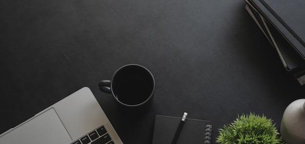 Colpo ambientale del posto di lavoro moderno scuro con il computer portatile e gli articoli per ufficio sulla tavola nera