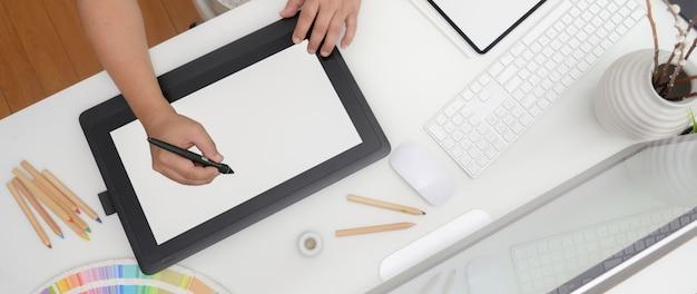 Colpo ambientale del progettista che lavora alla compressa digitale, al dispositivo del computer e ai rifornimenti del progettista