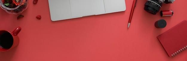 Colpo ambientale dell'area di lavoro con lo spazio della macchina fotografica, degli articoli per ufficio, del computer portatile e della copia sulla tavola rosa