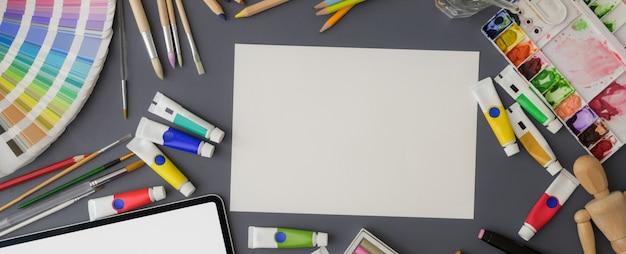 Colpo ambientale dell'area di lavoro con strumenti di schizzo di carta, campione di colore, tablet e pittura