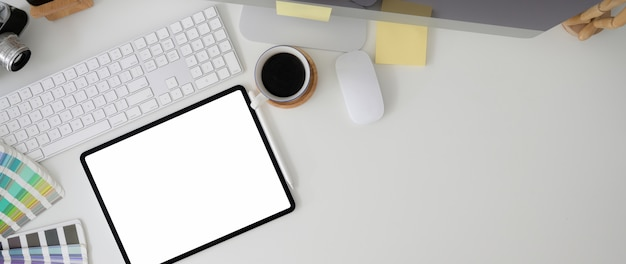 Colpo ambientale dell'area di lavoro con tablet, dispositivo informatico, forniture di design e copia spazio