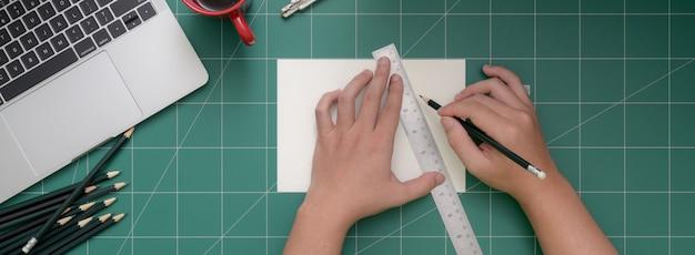 Colpo ambientale della carta da taglio dello studente con la taglierina sulla stuoia di taglio