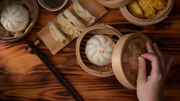 Colpo ambientale della mano femminile che apre seamer di bambù per mangiare i panini e gli gnocchi cotti a vapore della carne di maiale