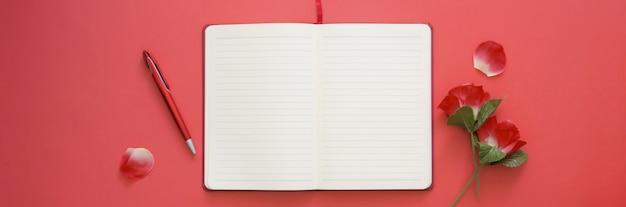 Colpo ambientale di area di lavoro creativa con lo spazio della copia e il taccuino aperto del diario sulla tavola rosa