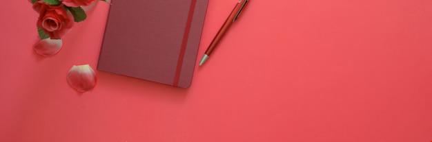 Colpo ambientale di area di lavoro creativa con lo spazio della copia e taccuino del diario sulla tavola rosa