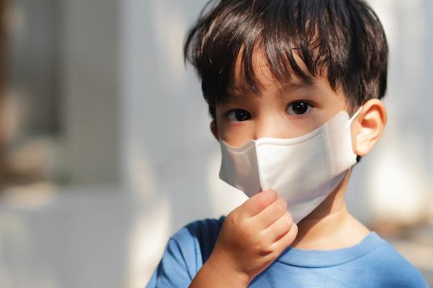 Colpo capo alto chiuso della maschera da portare del bambino. ragazzino asiatico nello scoppio del virus corona e nel concetto di crisi di pm 2.5.