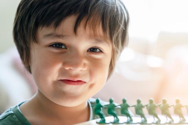 Colpo capo del ragazzo felice del bambino che esamina macchina fotografica con il fronte sorridente