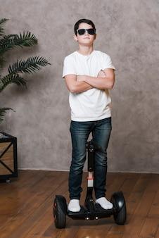 Colpo completo del ragazzo moderno con gli occhiali da sole su hoverboard