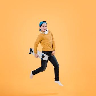 Colpo completo del ragazzo moderno con skateboard