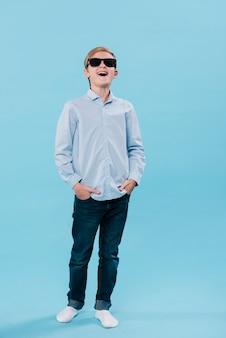 Colpo completo del ragazzo moderno sorridente che posa con gli occhiali da sole