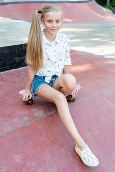 Colpo completo della ragazza che si siede sullo skateboard