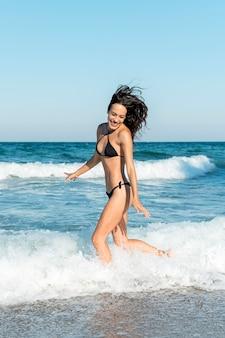 Colpo completo di bella ragazza in spiaggia