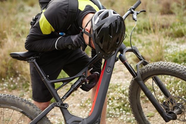 Colpo corto del motociclista maschio in casco e guanti che controlla i sistemi sulla e-bici nera, sporgendosi in avanti sopra il suo veicolo a motore a due ruote. giovane ciclista che ripara o che ripara pedelec in foresta