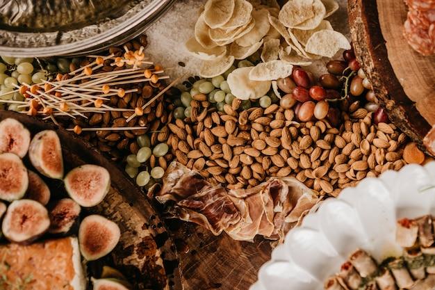 Colpo dall'alto di un tavolo pieno di mandorle, prosciutto, fichi e frutta secca