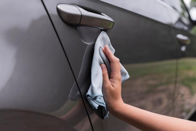 Colpo del primo piano con una mano che pulisce l'automobile