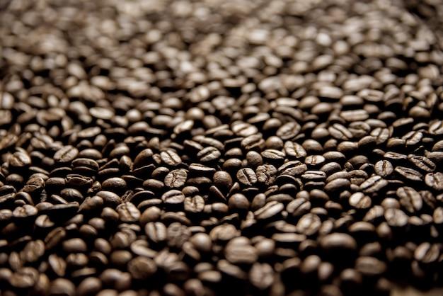 Colpo del primo piano dei chicchi di caffè con uno sfondo sfocato grande per sfondo
