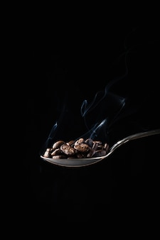Colpo del primo piano dei chicchi di caffè in un cucchiaio con fumo su oscurità