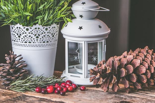 Colpo del primo piano dei chicchi di caffè rossi e un pinecone con una lanterna della candela su una superficie di legno