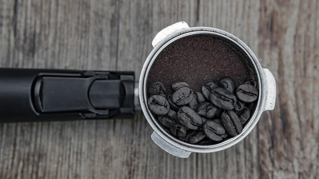 Colpo del primo piano dei chicchi di caffè su una polvere di caffè - ottimo per lo sfondo o il blog