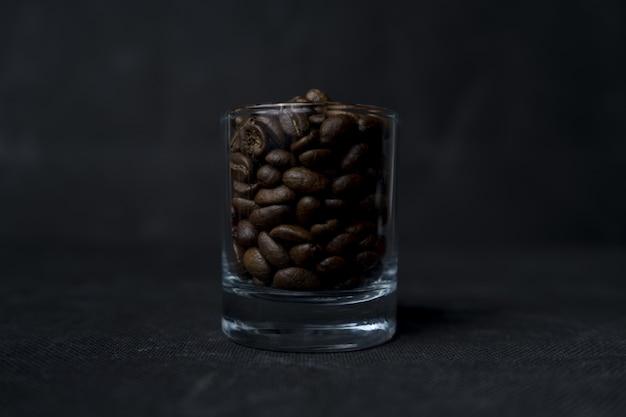 Colpo del primo piano dei chicchi di un bicchiere di caffè su una superficie scura